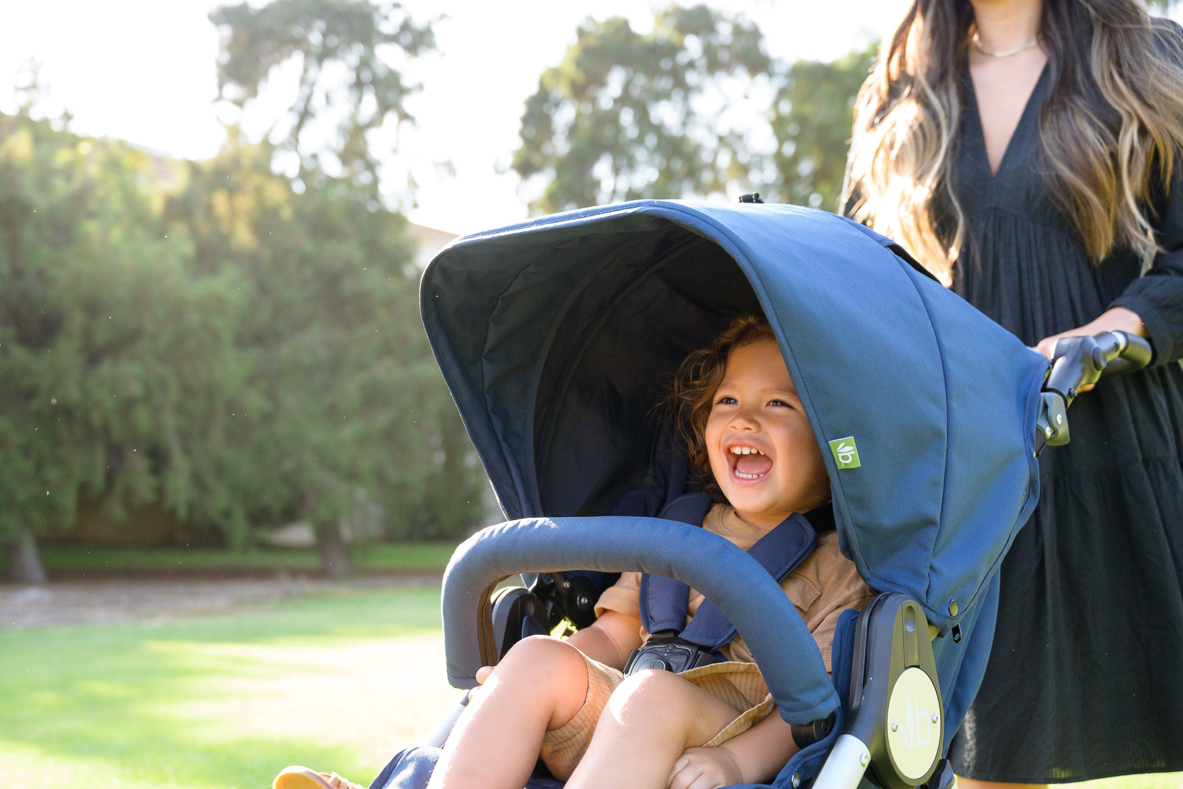 Photo of smiling child closeup inside the canopy of Bumbleride Indie stroller in Maritime Blue