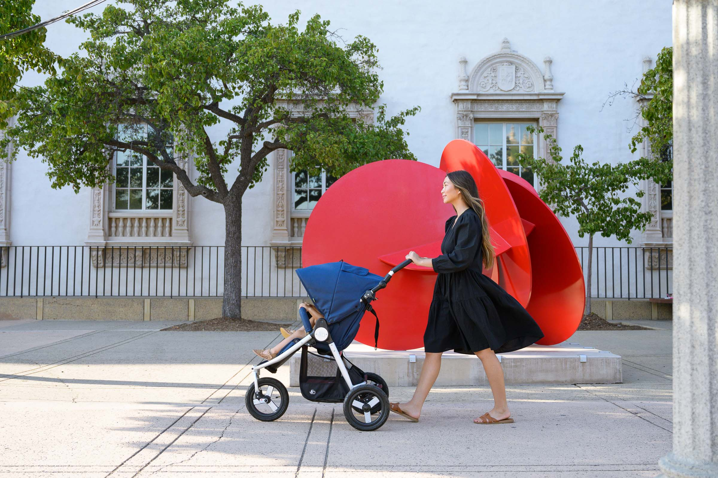 Photo of mother in black dress pushing Indie stroller in Maritime Blue with bright red circular sculpture in background