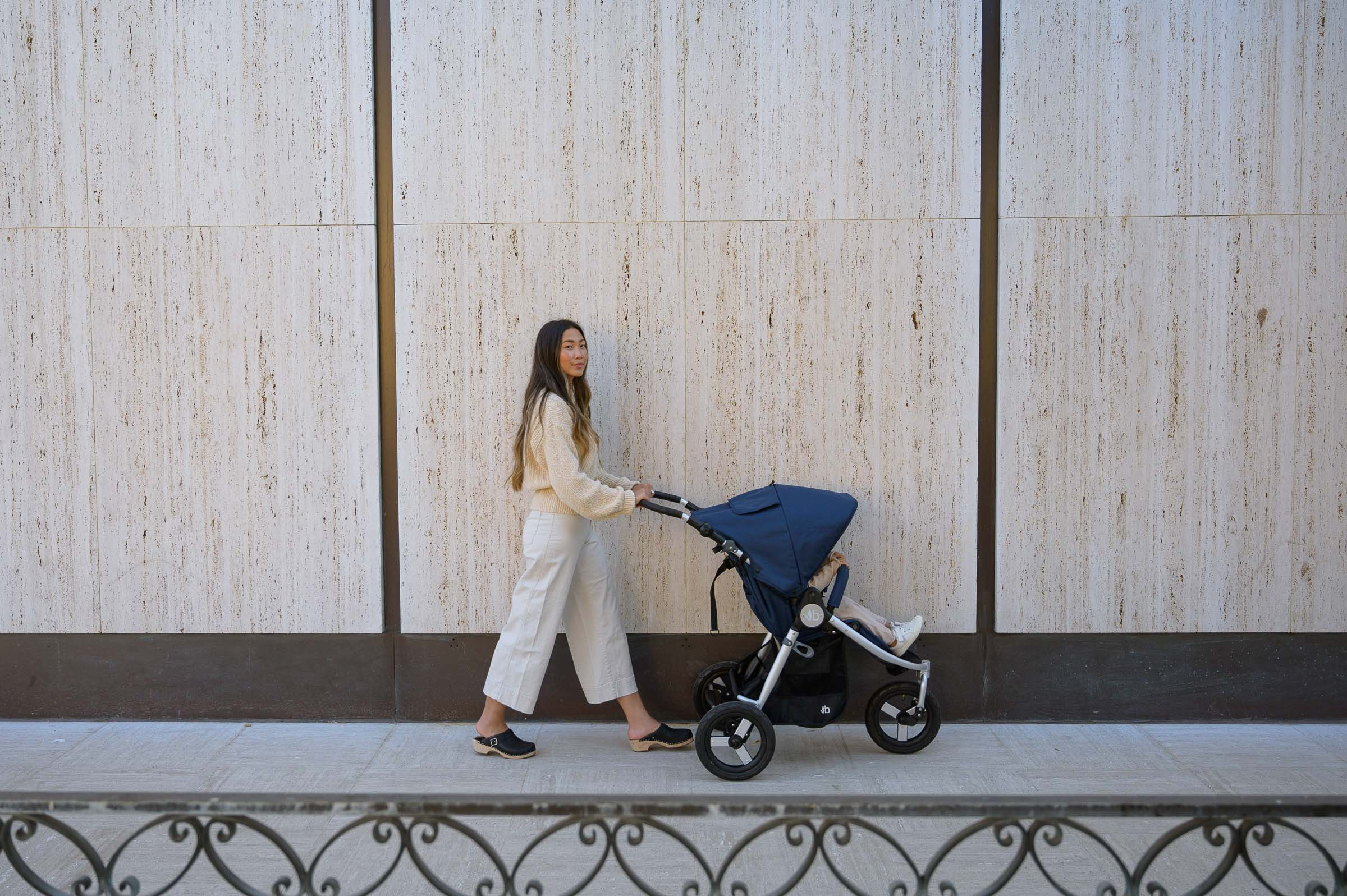 Photo of mother pushing child in Indie in Maritime Blue with white wall in background and cement terrain