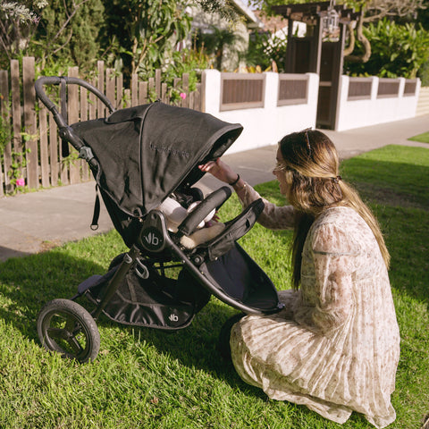 Bumbleride Indie in Matte Black with child inside and mom kneeling in front of talking to child.