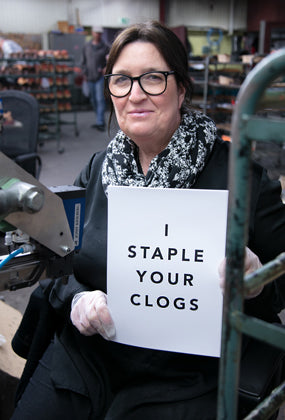 Woman holding a sign that reads: I staple your clogs