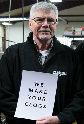 Man holding a sign that reads: We make your clogs