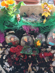 Painted stones in a fairy garden