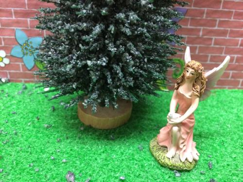 Kneeling ceramic fairy in pink dress