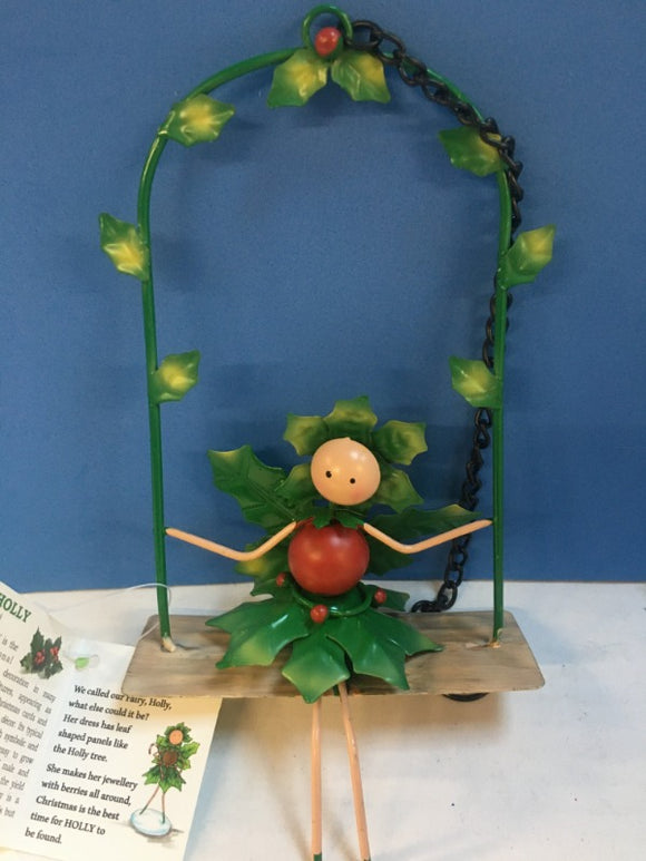 metal fairy sitting on a swing decorated with holly