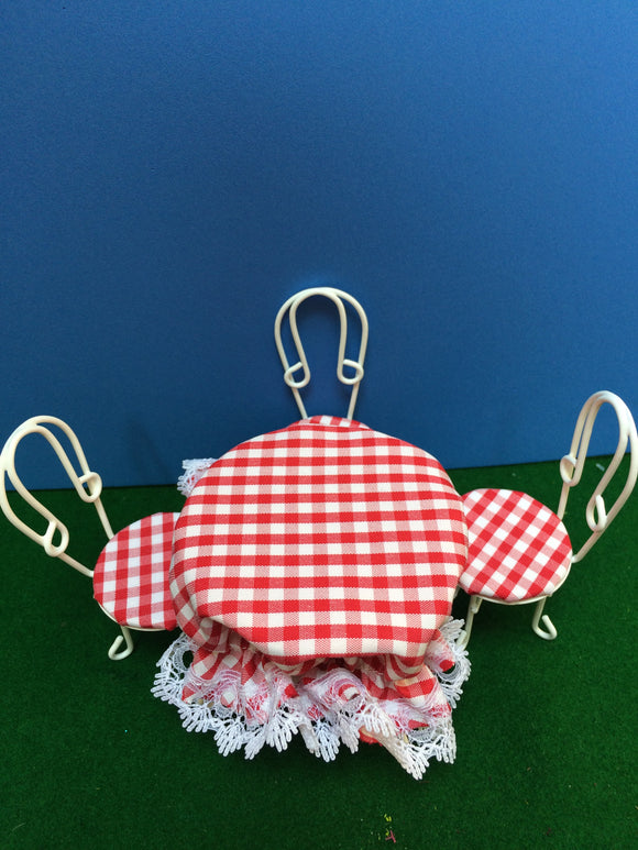 White wire table with four chairs, red check cloth perfect for an outdoor wedding