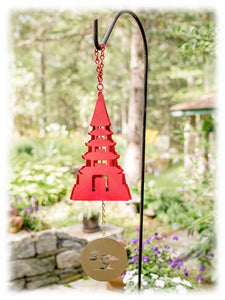 The red steel meditation bell is shown hanging from a black metal rod with the gold-colored bottom sail below. The bell is shaped to resemble a classic Japanese pagoda, with the entire hanging bell and sail set against a background of flora and fauna.
