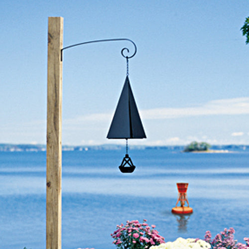 A flat black steel wind bell in the shape of a pyramid hangs from a bracket in front of a scene of open water and a red buoy