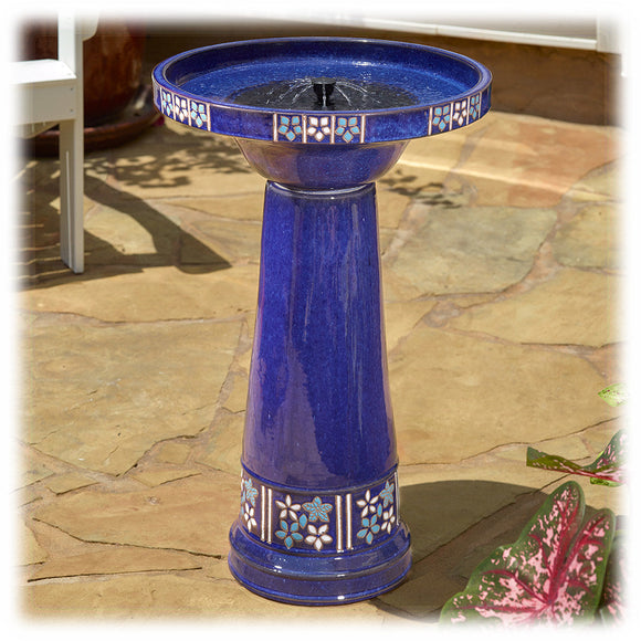 This image shows a bright cobalt blue ceramic birdbath operating as a solar fountain, with a 360° spray of water coming out in the basin. It's set on a patio or outdoor stone setting, with a background of flowers and a deck chair.