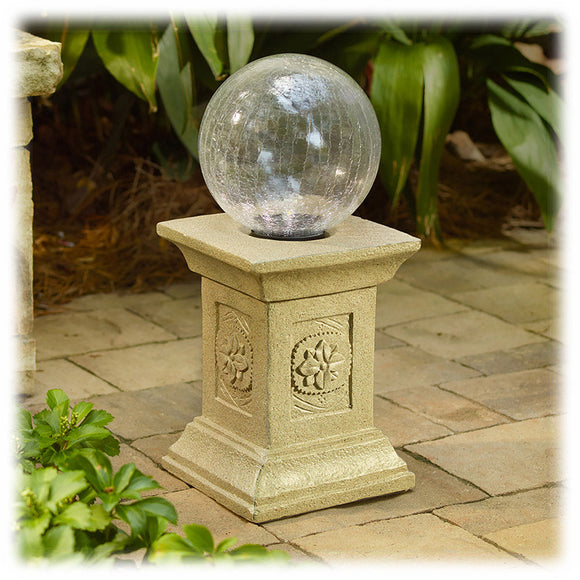 A square tan colored pedestal with a floral design on each side holds a crackled glass gazing globe