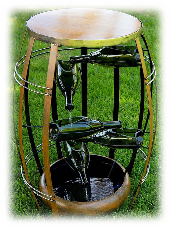 Multi-leve green wine bottles inside of oval metal cage pouring outdoor fountain