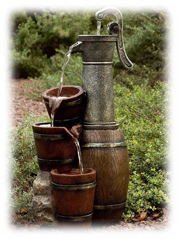 An old style silver hand pump pours water into a series of faux wood barrels in this outdoor water feature