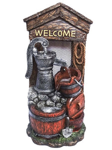 "A wall bears the message ""Welcome"" while a hand pump pours water into a two tiered old west barrel fountain"