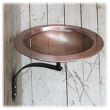A shiny Copper Bird Bath bowl shown mounted on a wall using a black metal bracket