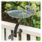 The scalloped edge bird bath basin is shown attached to the black wrought iron center rail hardware and attached to a porch rail