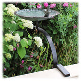 The brass and verdigris colored basin is shown attached to the side rail black wrought iron hardware kit and attached to a rail with a bed of flowers in the background