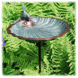 A close-up view of the brass and verdigris colored bird bath basin with scalloped edges attached to a plain black grounding stake surrounded by green ferns