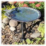 The scalloped edges of the brass and verdigris colored bird bath bowl are shown with the basin attached to a black wrought iron 3-legged stand and sitting in the earth surrounding by pebbles and plants