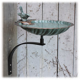 A view of the scalloped edge bird bath basin with verdigris and brass color finishes shows the bowl attached to the wall mounting hardware via the threaded nib and attached to a wall