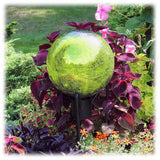 "This light green colored 10"" diameter hand blown crackled glass globe is shown paired with a short black metal stand surrounded by some colorful red and purple flowers and greenery."