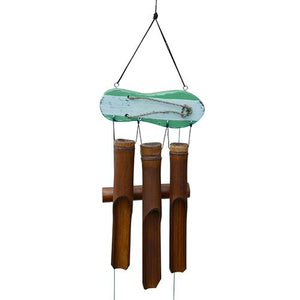 This brown bamboo wind chime has a pastel colored flip flop topper element that hangs horizontally above the 3 dark brown bamboo tubes. It's shown on a white studio background.
