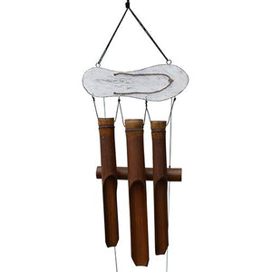 This naturally colored brown bamboo wind chime has an off-white flip flop topper element that hangs horizontally above the 3 dark brown bamboo tubes. It's shown on a white studio background.