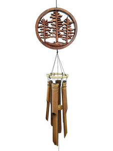 "The naturally colored bamboo wind chime has a 7"" circular ""Forest Trees"" topper element above the 5 brown bamboo tubes. It's shown hanging with a white studio background."