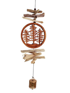 "This handmade mobile features a circular carved ""Forest Trees"" element with natural driftwood above and below it. At the bottom is a single, hand made metal bell. It's shown hanging on a white studio background."