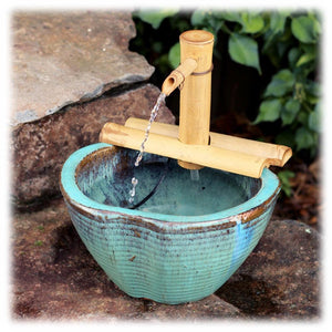 This image shows the semi-circular 2-branch natural bamboo spout sitting atop a antique washed turquoise colored ceramic basin. It is shown placed on some rocks, spitting a stream of water. The background has some foliage and rocks pictured.