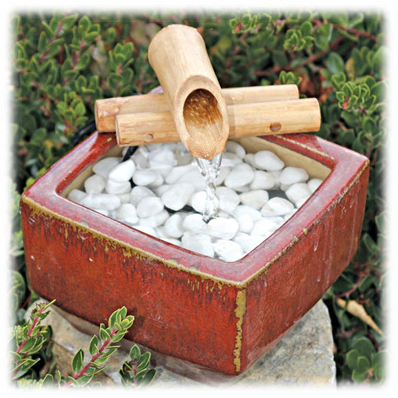 This image shows a traditional small bamboo spout attached to 2 bamboo arns sitting on top of a square, antique red glazed ceramic basin. It is shown sitting on a flat rock, with white pebbles inside the basin, and a stream of water gently flowing from the spout into the basin. The background has a variety of greenery surrounding it.