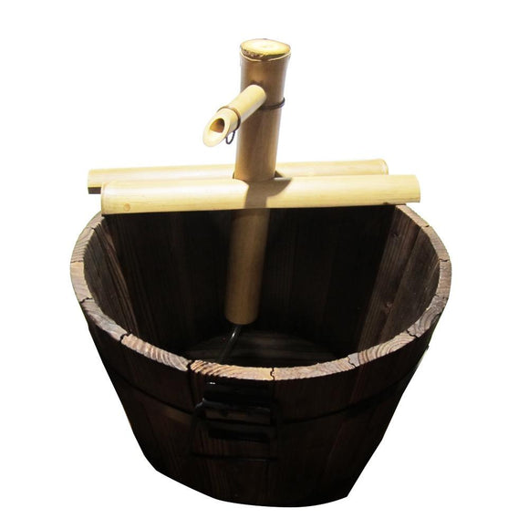 This image shows the semi-circular 2-branch natural bamboo spout sitting  on top of a rustic wood basin. It is shown on a white studio background.