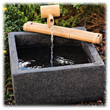This image shows a traditional natural bamboo spout resting on two long bamboo branches. It is shown sitting  on top of a square gray ceramic basin, spilling water into the reservior. It's surrounded by some greenery on all sides.