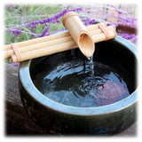 This image shows a large bamboo spout attached to 3 bamboo canes sitting atop a round ceramic basin. It is shown placed on a wood board, with a stream of water pouring into the basin. The background has some lavender foliage surrounding it.