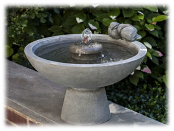 This large, elegant birdbath style fountain is cast from high density stone. Shown in the greystone finish, it features a bubbling center element, with playful bird elements on the side of the basin. Shown placed on a small ledge, garden greenery can be seen behind it.