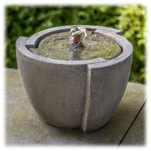 A bubbling tabletop fountain made of cast concrete is shown set on an outdoor flagstone with greenery in the background. The oval shaped base tapers outward as it rises, with a unique interlocking pattern at the top, where water bubbles up.