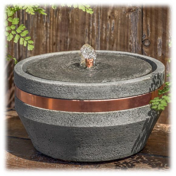 This circular bubbling tabletop fountain is made of cast concrete with a shiny copper band circling around the top. It is shown set on an outdoor flagstone with greenery in the background. The round  base tapers outward as it rises, with a copper spout bubbling water in the top basin.