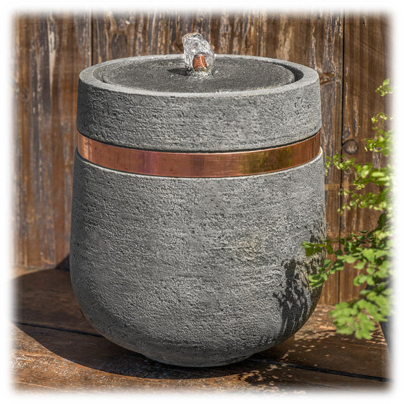 This oval shaped bubbling tabletop fountain is made of cast concrete with a shiny copper band circling around the top. It is shown set on an outdoor flagstone with greenery in the background. The narrow  base tapers outward as it rises, with a copper spout bubbling water in the top of the basin.