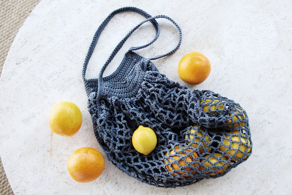 A crocheted market bags is laying on a marble surface with a bunch of lemons