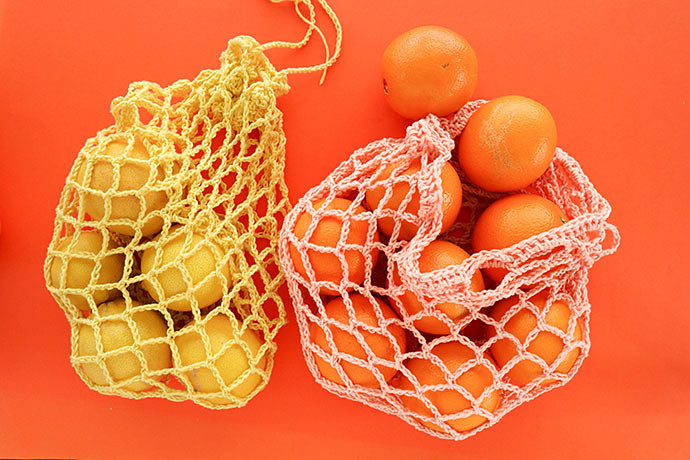 two bags of citrus fruit on a bright orange backdrop. The fruit are in crocheted reusable produce bags