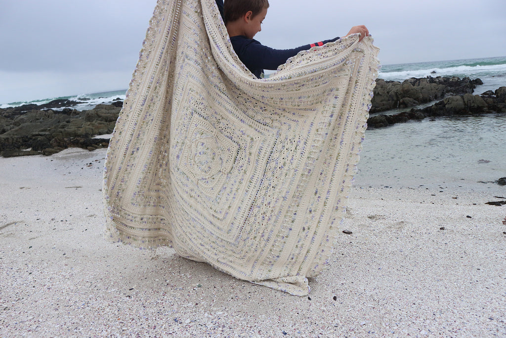 A young child stands on a beach holding up a knitted blanket