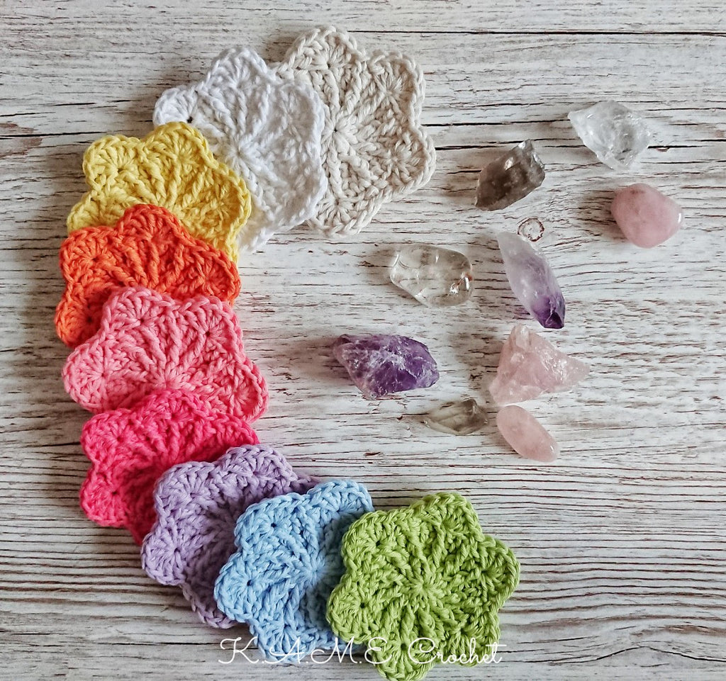 A collection of crocheted face scrubbies sits on a wood counter with a collection of crystals