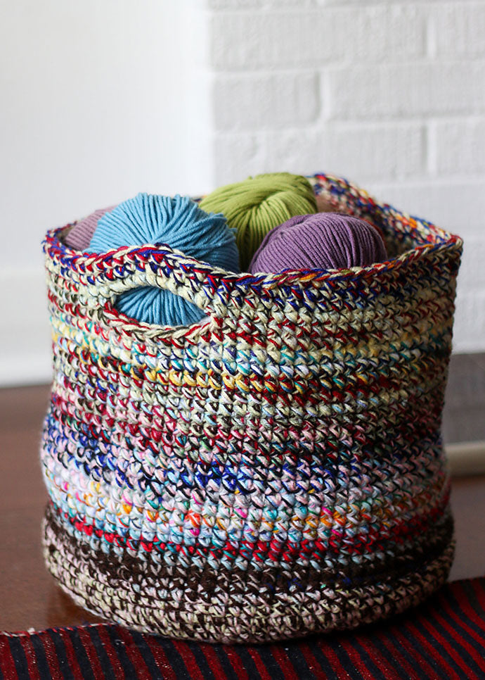 A colourful basket made of yarn is sitting on a wood table. Balls of wool fill the basket