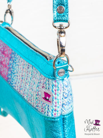 Close up photo of Mad Hatter Warped & Woven Hartley Handbag with Teal Metallic leather and a cool toned colourway.