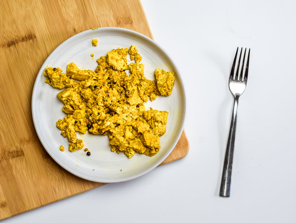a plate of yellow turmeric tofu sits on a cutting board with a fork next to it