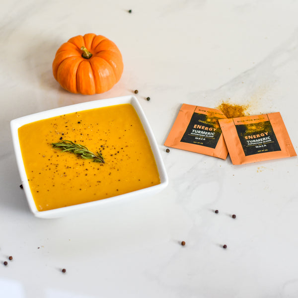 A square bowl of orange soup sits on a white table with a small pumpkin and goldynglow packets next to it.