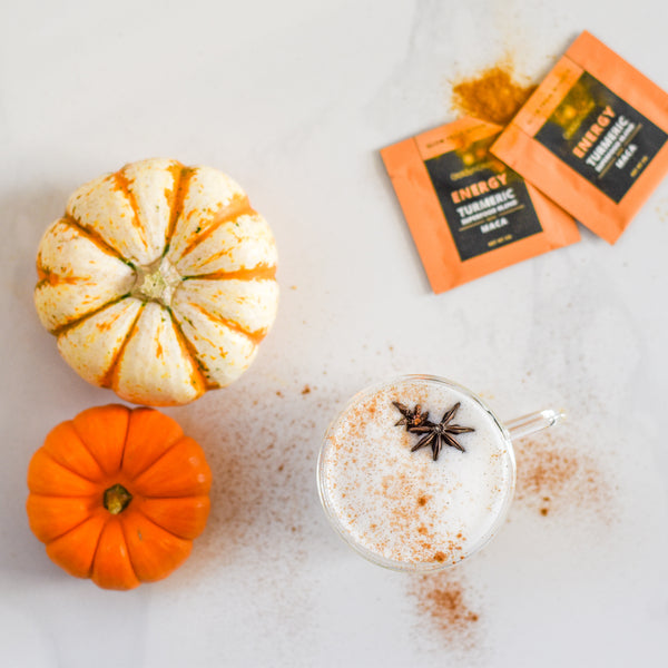 a pumpkin spice superfood latte sits on a table with a pumpkin and goldynglow energy packets