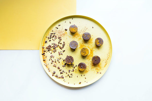 Yellow plate sits on a marble counter. There are chocolate cups sprinkled with turmeric powder on the plate and cocoa nibs surrounding that.