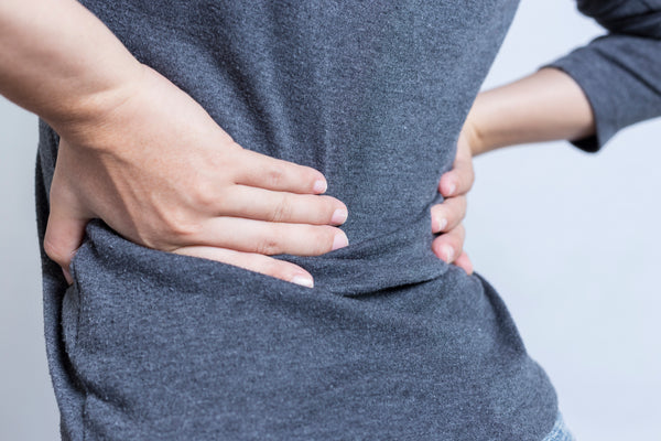 woman holds her lower back in pain