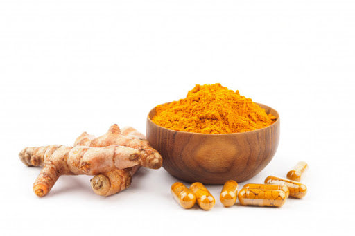 There is a bowl of turmeric powder next to tumeric root and supplements or curcumin on a white surface