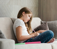 Girl Writing on Couch